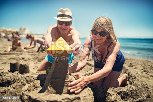 Happy senior couple playing in sand on beach. They are building sandcastle. In the background grandchildren are playing. Sunny summer day.