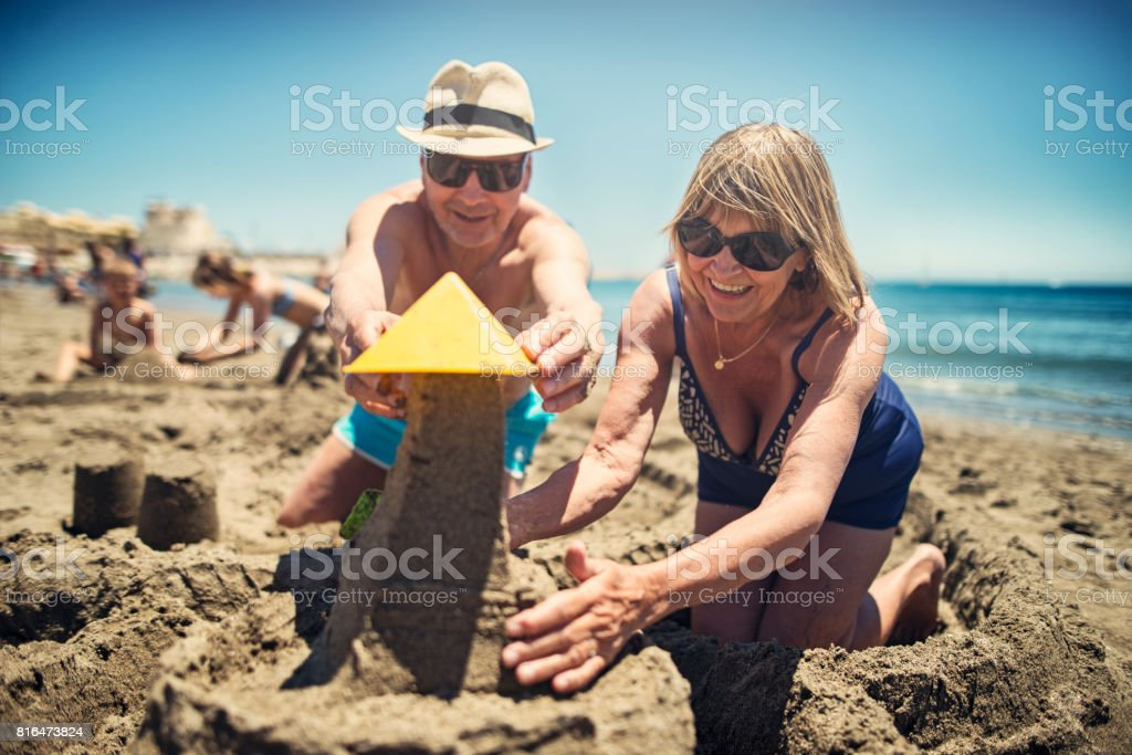 Happy senior couple playing in sand on beach stock photo