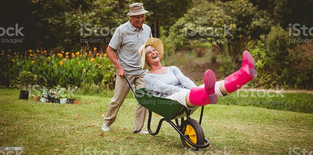 Happy senior couple playing with a wheelbarrow​​​ foto
