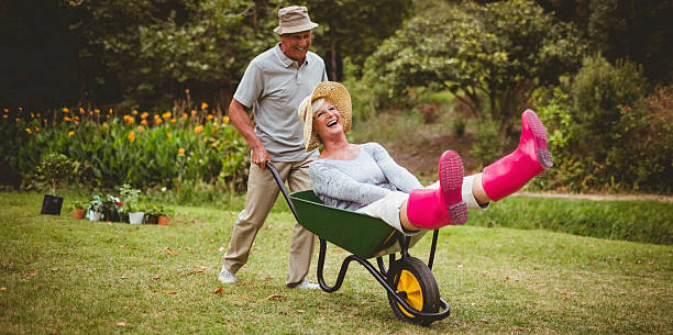 happy senior couple playing with a wheelbarrow - kruiwagen stockfoto's en -beelden