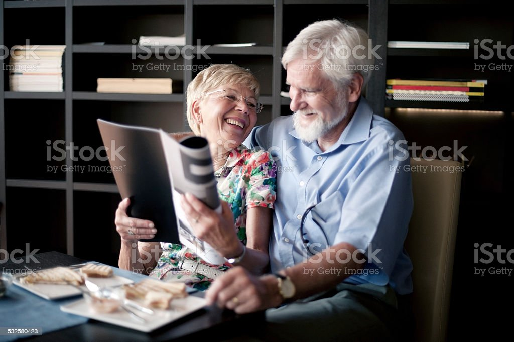 Happy Senior Couple Reading Magazine in Bar royalty-free stock photo