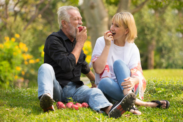 Happy senior couple relaxing in park eating apple together morning time. old people sitting on grass in the autumn park . Elderly resting .mature relationships. family stock photo