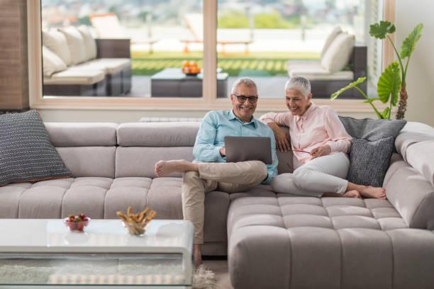 brautpaar senioren am sofa zu hause entspannen und laptop verwenden. - seniorenwohnungen stock-fotos und bilder