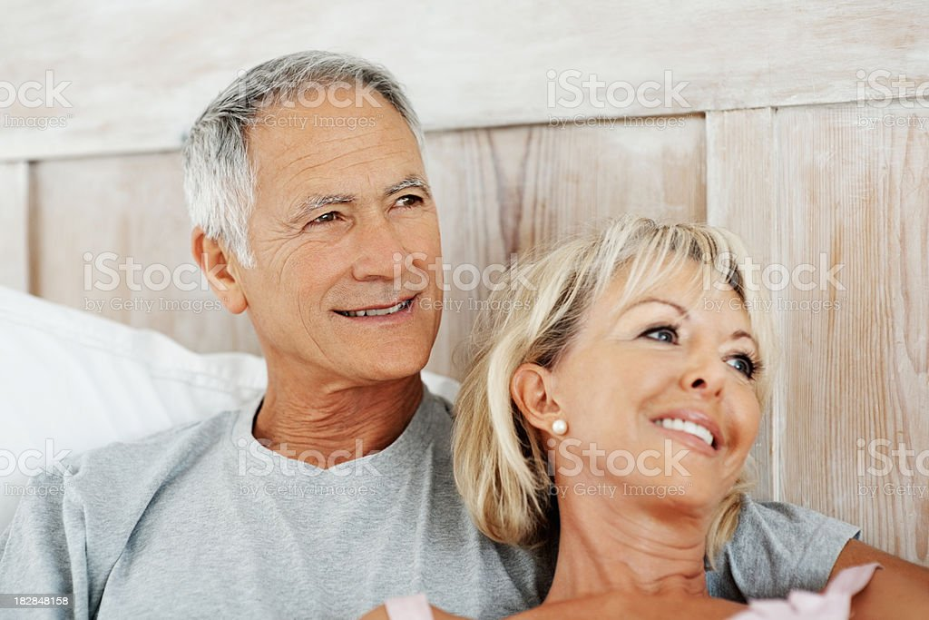 Happy senior couple relaxing together in bed royalty-free stock photo
