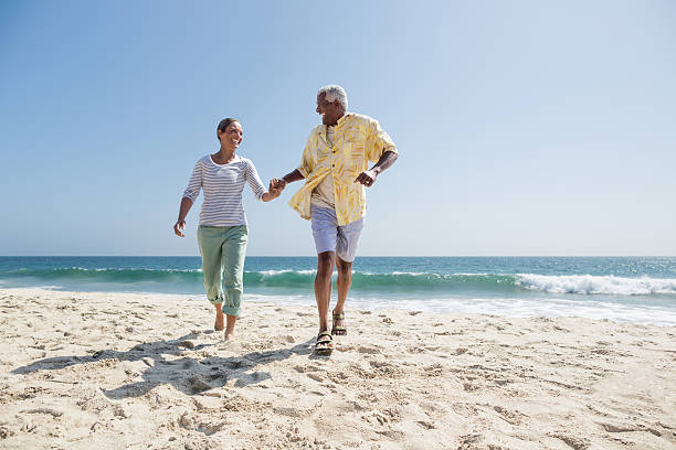 Happy senior couple running on the beach stock photo
