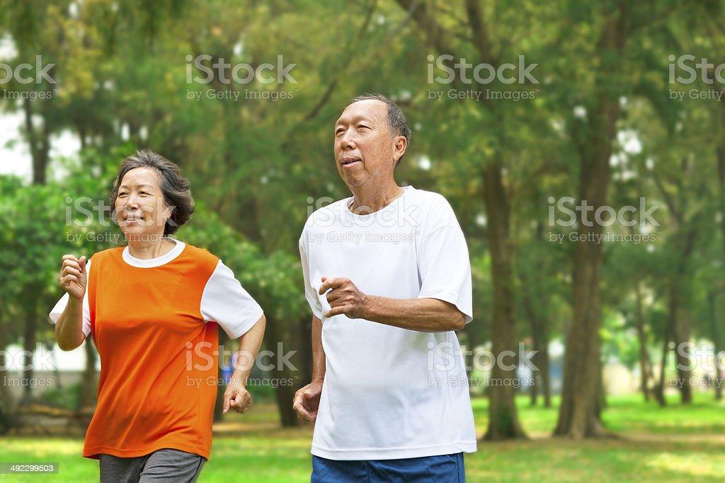 happy senior couple running together stock photo