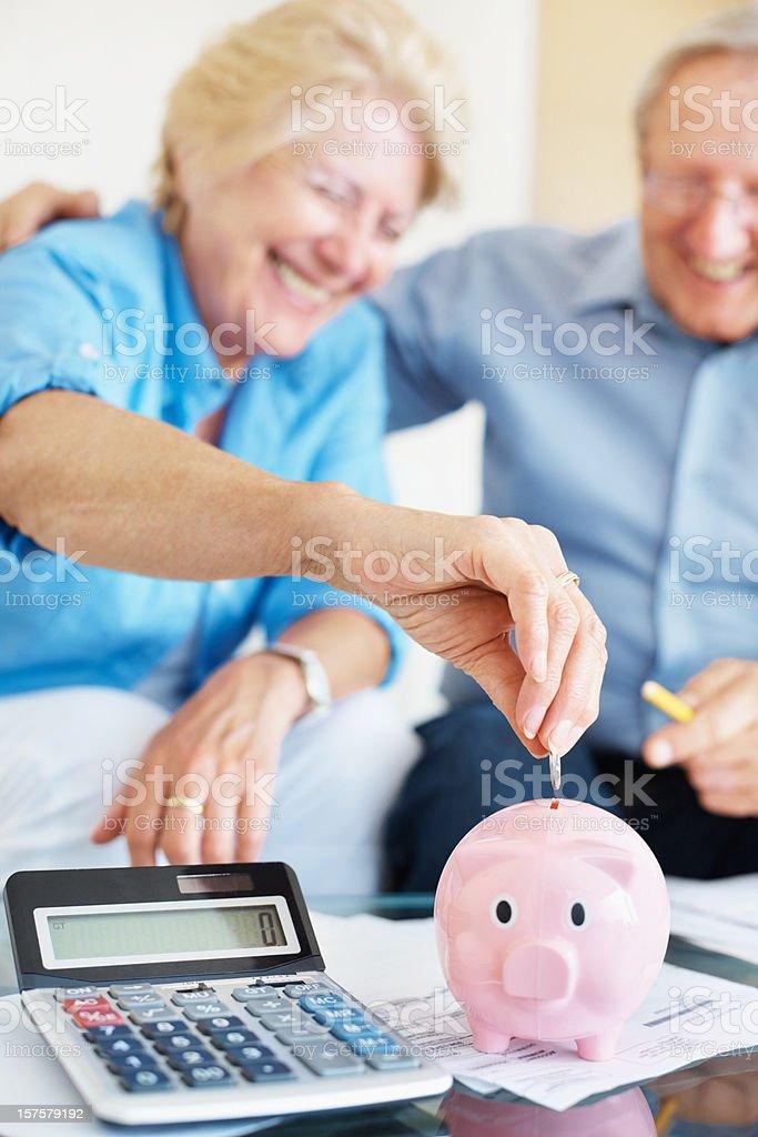 Happy senior couple saving money at home royalty-free stock photo