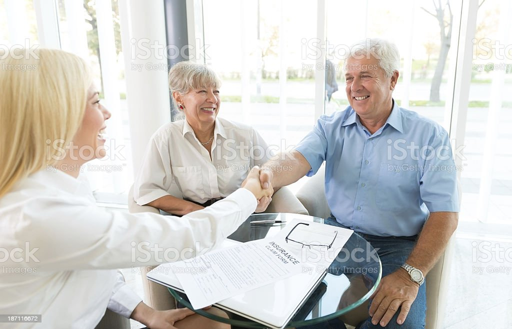 Happy senior couple shaking hands with lady insurance agent royalty-free stock photo