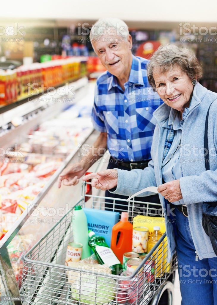 Happy Senior Couple Shopping For Frozen Food In Supermarket