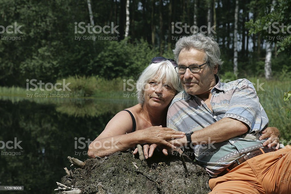 Happy Senior Couple sitting in front of a Pond royalty-free stock photo