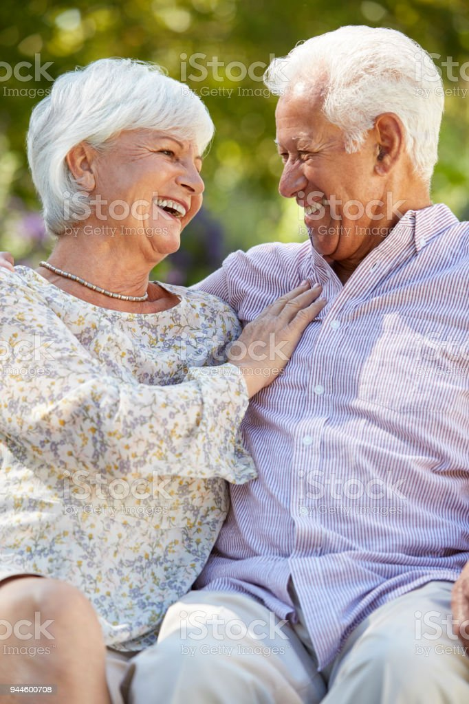 Happy senior couple sitting in garden looking at each other стоковое фото