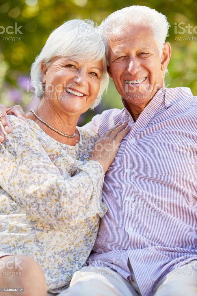 Happy senior couple sitting in the garden embracing стоковое фото