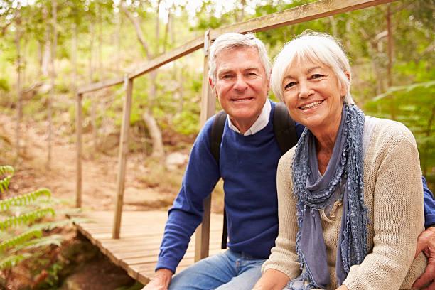 feliz pareja mayor sentado en un puente en el bosque, vertical - pareja mayor fotografías e imágenes de stock
