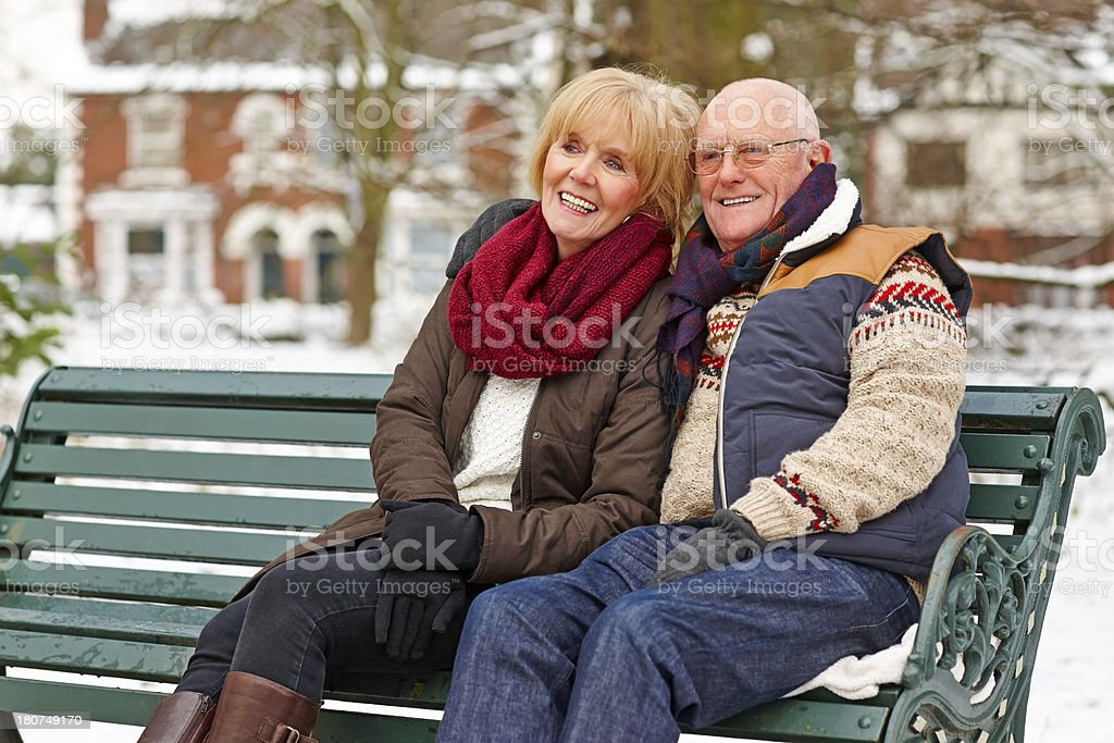 Happy senior couple sitting on a park bench royalty-free stock photo