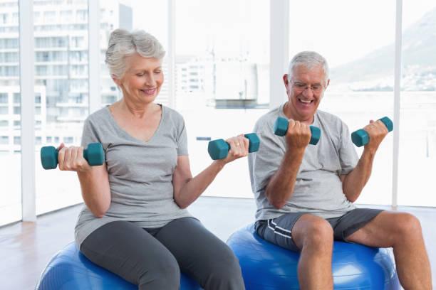 Happy senior couple sitting on fitness balls with dumbbells - foto stock