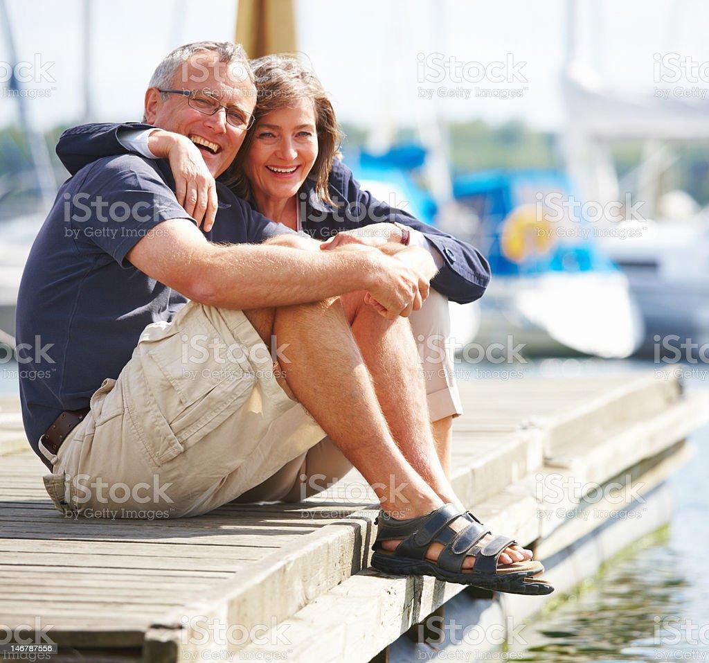 Happy senior couple sitting on quay by sea royalty-free stock photo