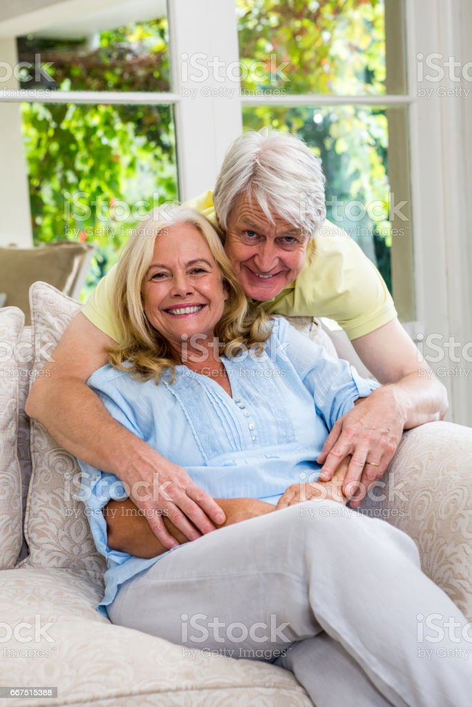 Happy senior couple sitting on sofa in living room at home foto stock royalty-free