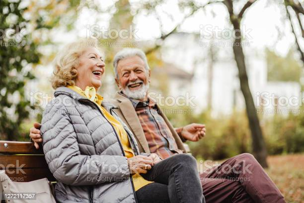 Photo of Happy senior couple sitting on the bench in park