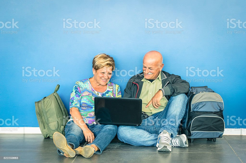 Happy senior couple sitting on the floor with laptop stock photo