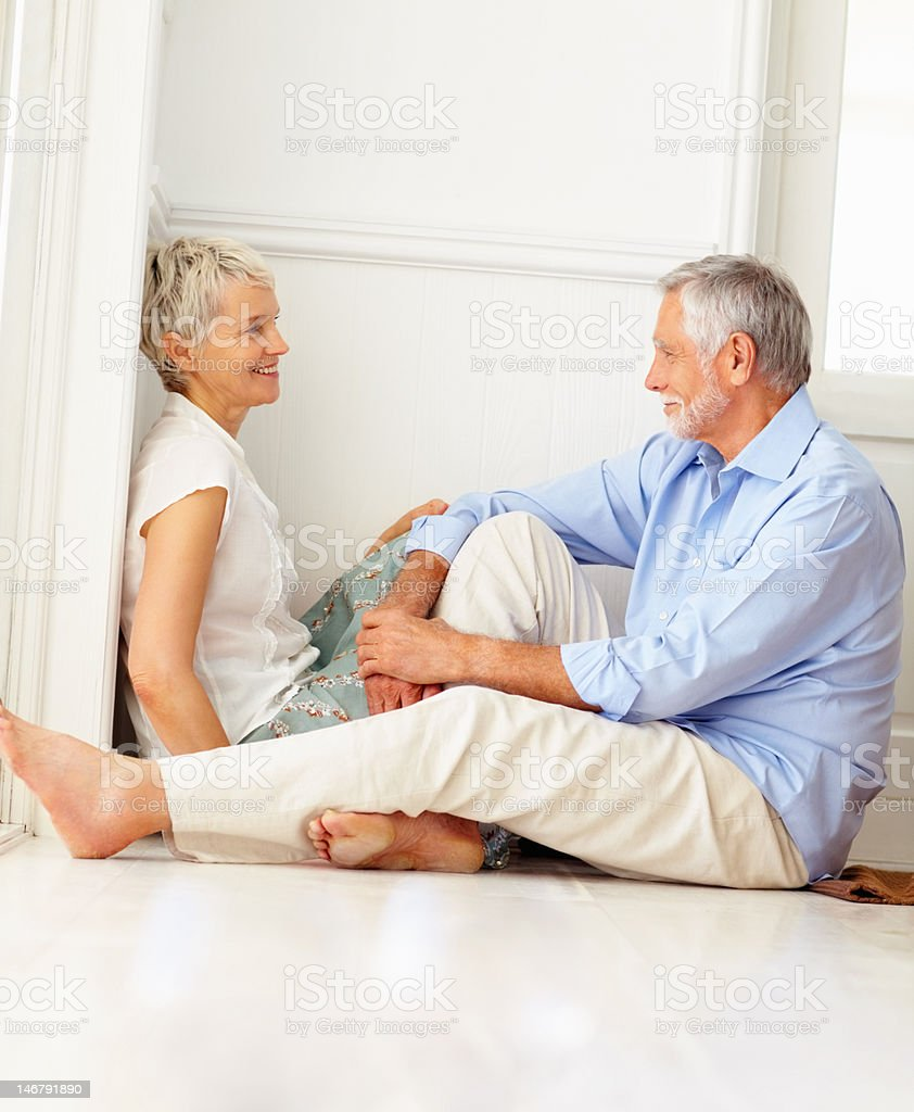 Happy senior couple sitting together and discussing royalty-free stock photo