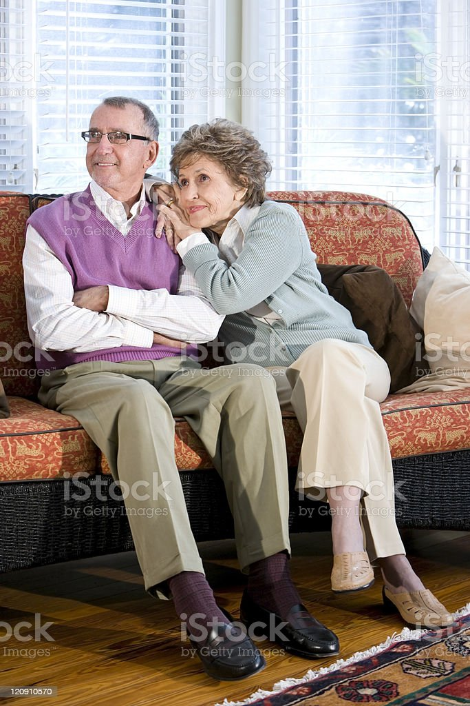 Happy senior couple sitting together on couch royalty-free stock photo