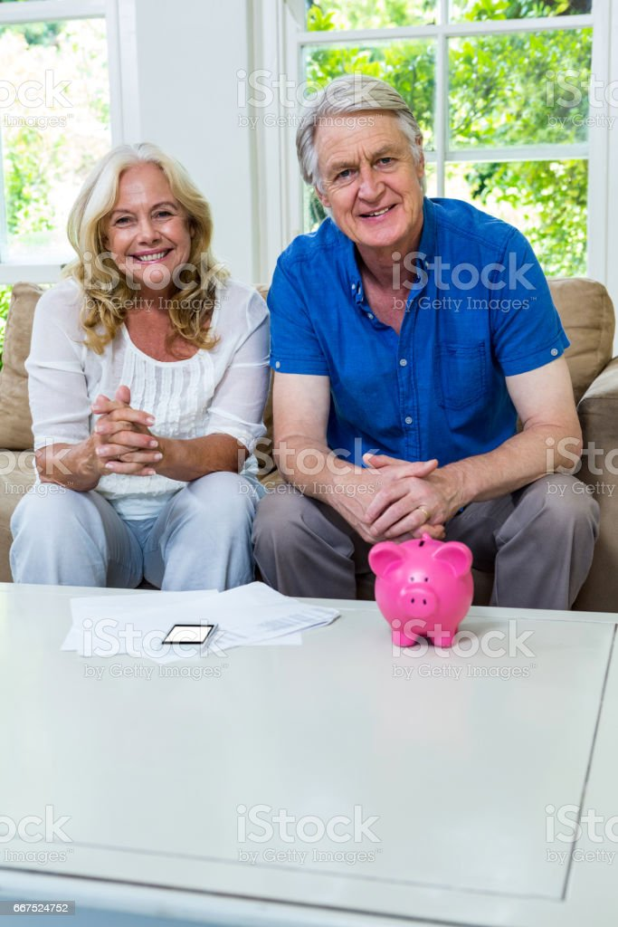 Happy senior couple sitting with piggi bank in living room at home stock photo