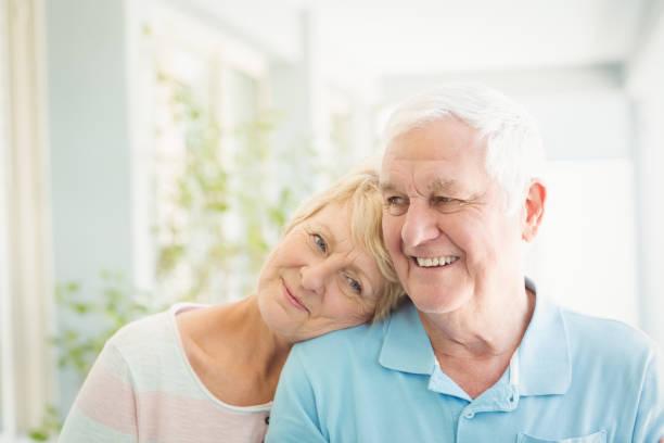 feliz pareja senior sonriente en su casa - pareja mayor fotografías e imágenes de stock