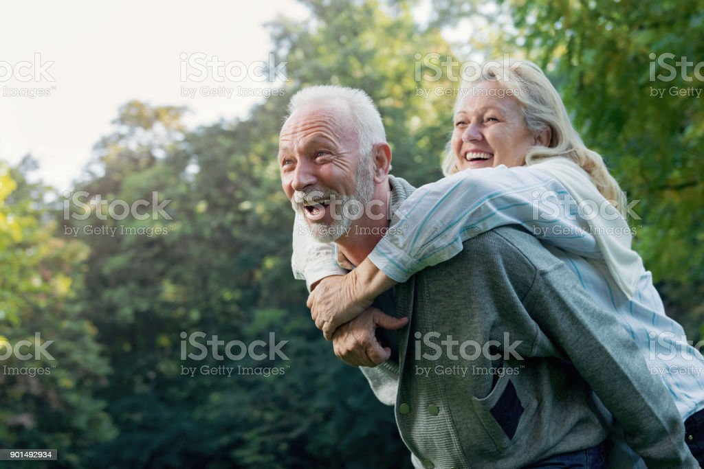 Happy senior couple smiling outdoors in nature royalty-free stock photo