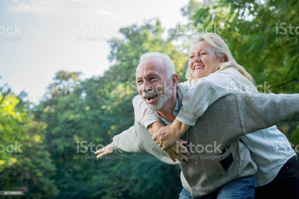 Happy senior couple smiling outdoors in nature stock photo