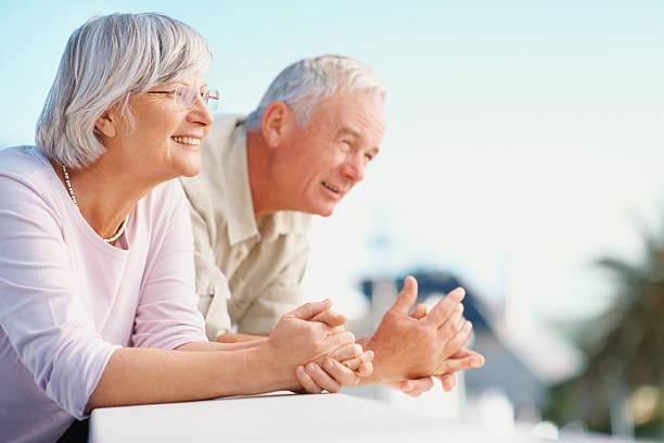 Happy senior couple standing at balcony stock photo