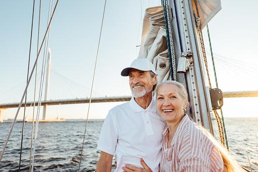 Happy senior couple standing at mast. Two smiling people enjoying boat trip.