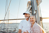 Happy senior couple standing at mast. Two smiling people enjoying boat trip.