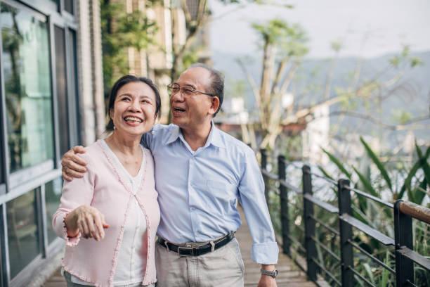 Happy senior couple standing on balcony at home stock photo