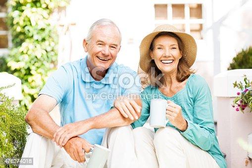 Portrait of happy senior couple taking coffee break while gardening in garden. Horizontal shot.