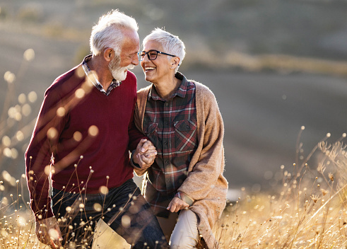 Happy senior couple talking while walking on a hill in autumn day.
