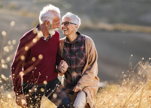 Happy senior couple talking while walking on a hill in autumn day. stock photo
