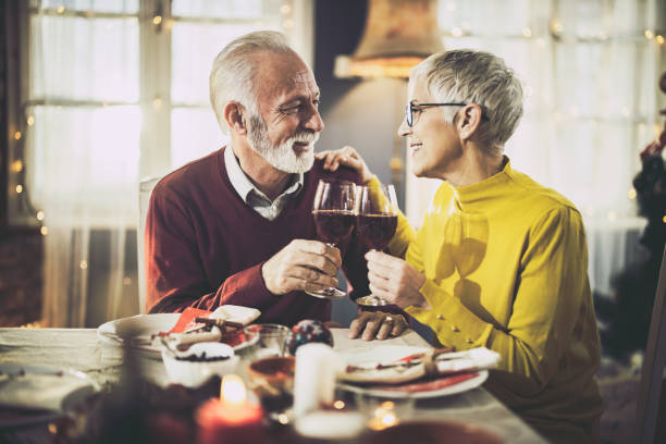 Happy senior couple toasting with wine during lunch at home. stock photo