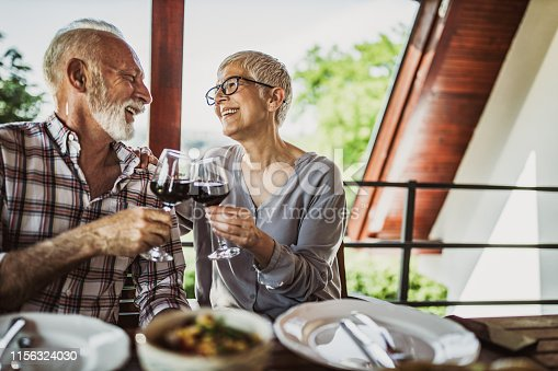 Happy mature couple communicating while toasting with red wine during their meal on a balcony.