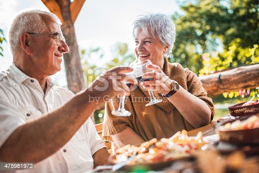 Smiling senior man and woman celebrating their anniversary. They are sitting on a restaurant terrace and toasting with red wine.