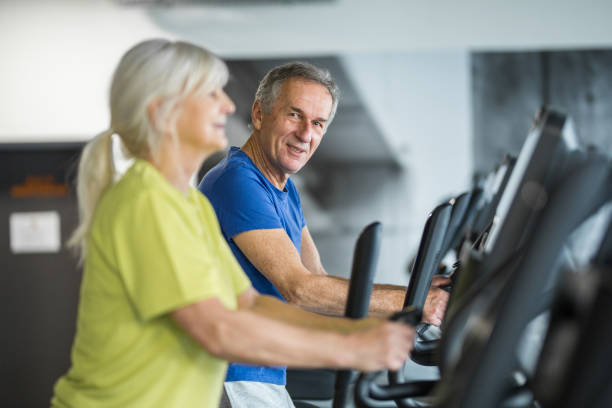 Happy senior couple training on stair stepper at gym stock photo