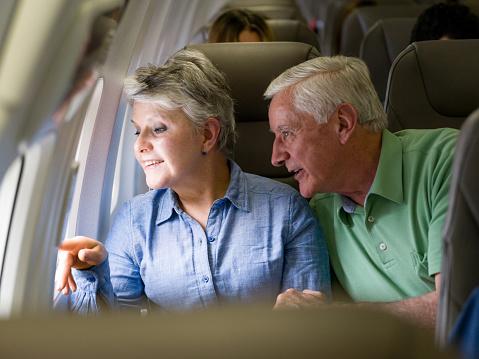 Happy senior couple traveling by plane