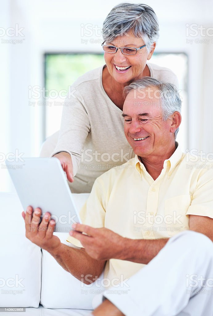 Happy senior couple using digital tablet at home royalty-free stock photo