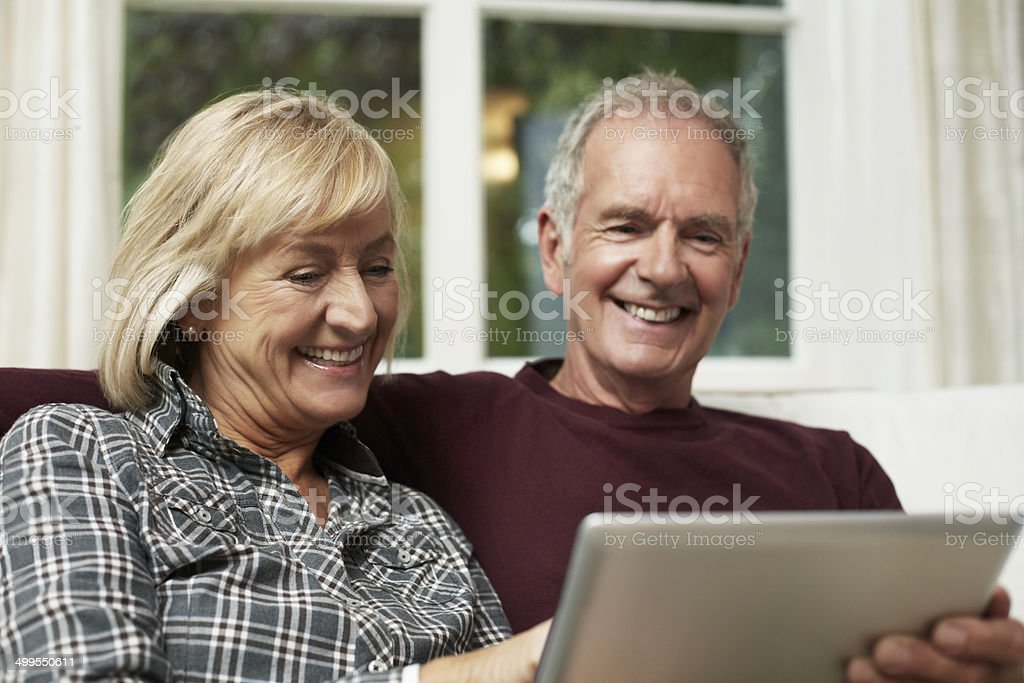 Happy senior couple using digital tablet stock photo