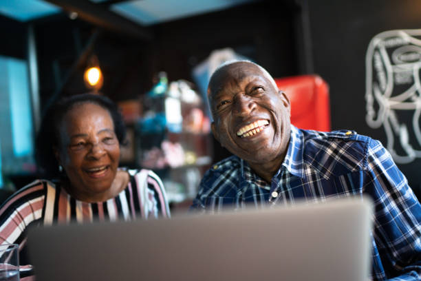 Happy senior couple using laptop in a restaurant Happy senior couple using laptop in a restaurant old man working in a pub stock pictures, royalty-free photos & images