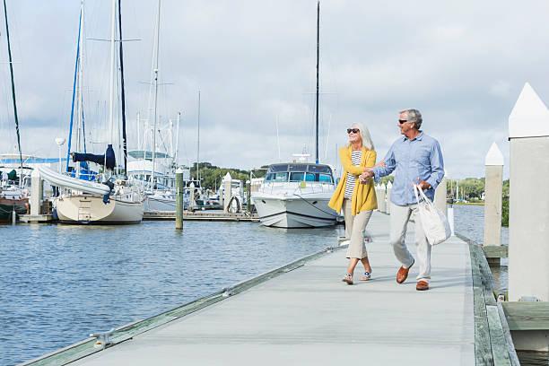 Feliz sênior casal andando de mãos dadas ao longo do porto - foto de acervo