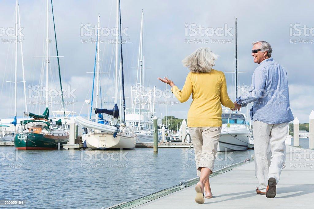 Happy senior couple walking along harbor holding hands stock photo