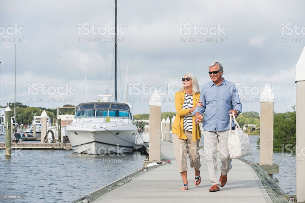 Happy senior couple walking along harbor holding hands stock photo