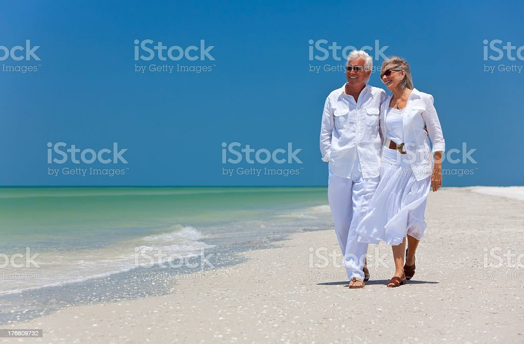 Happy Senior Couple Walking on A Tropical Beach royalty-free stock photo