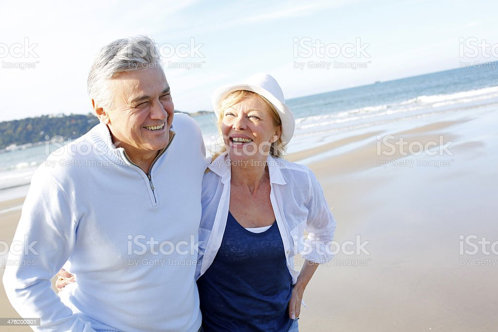 Happy senior couple walking on beach stock photo