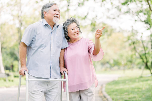 Happy senior couple  walking with walker in the park stock photo
